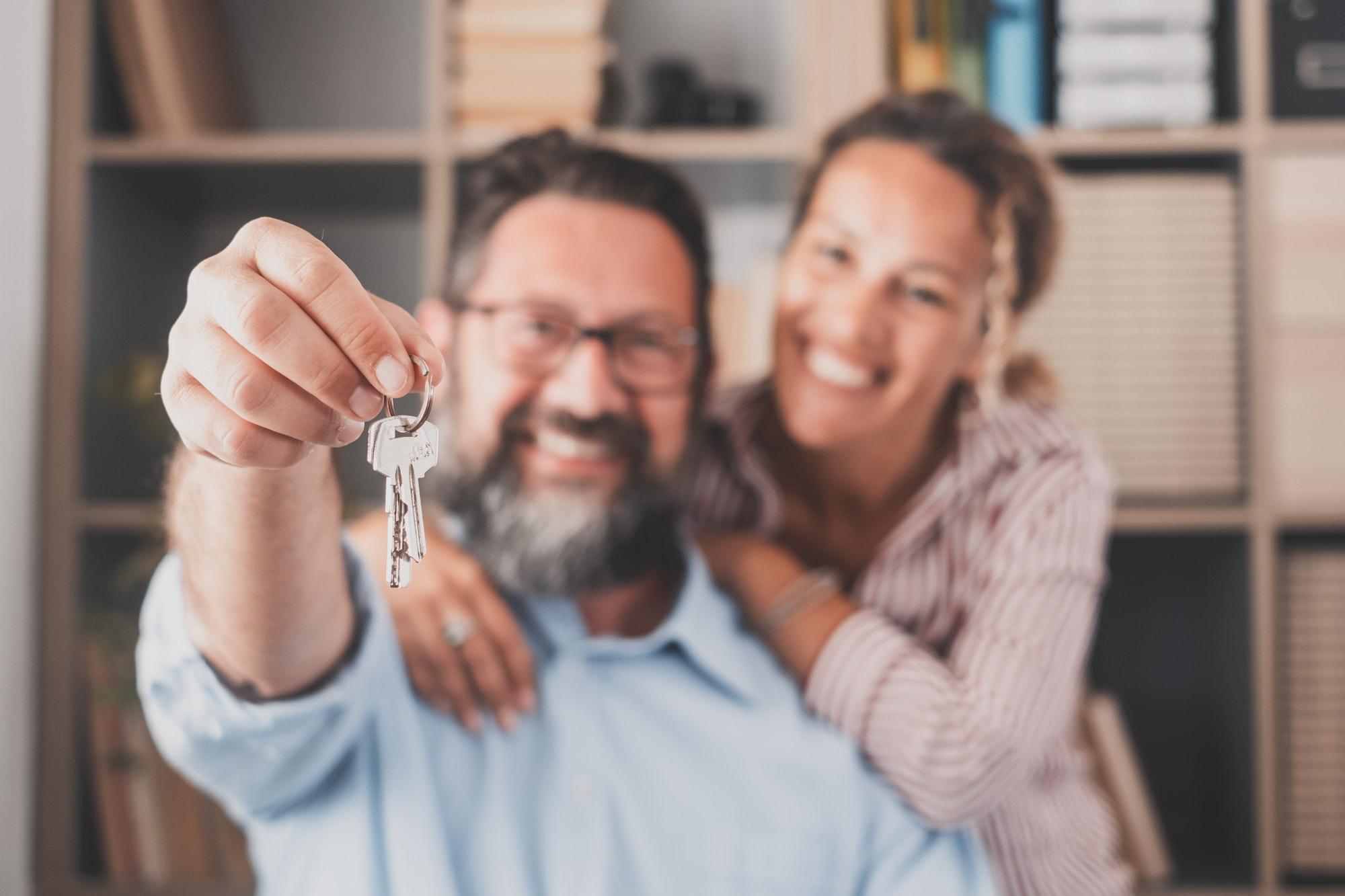 Focus on keys, held by excited young spouses homeowners. Happy married family couple