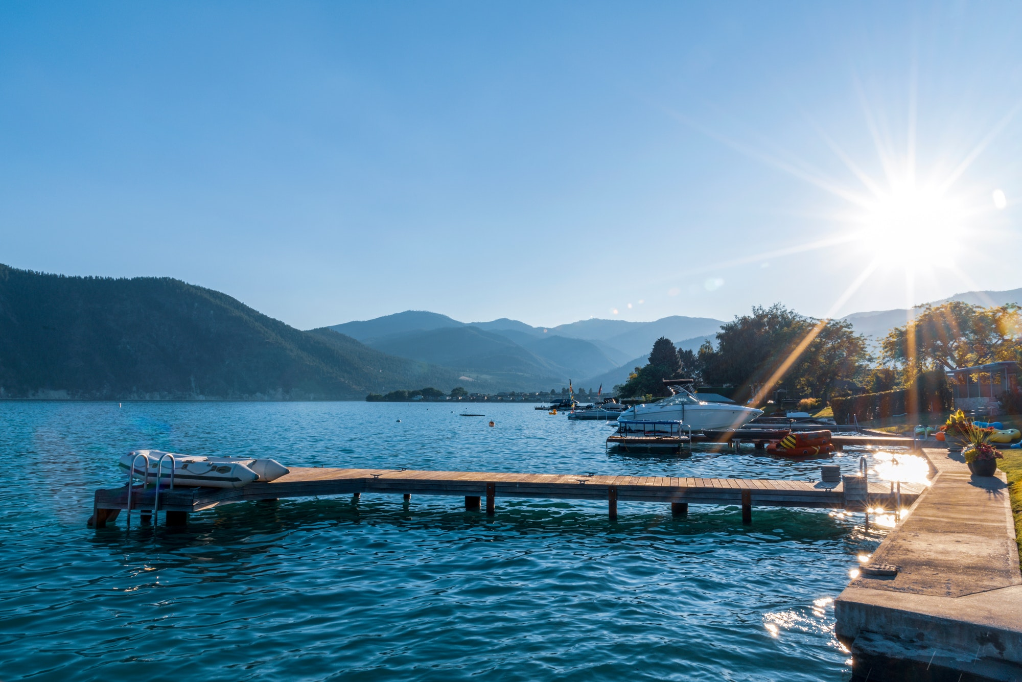 Lake shore boat dock with small inflatable dingy raft late day sunburst sunshine over mountains.